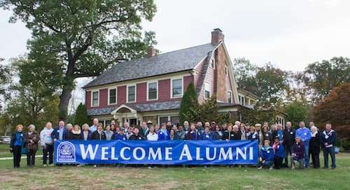 People posing with a Welcome Alumni banner
