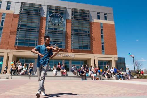 A student playing a violin in front of Buley