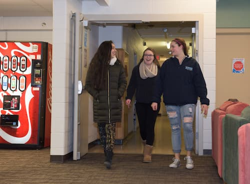 Three students walking into Chase dormitory common area