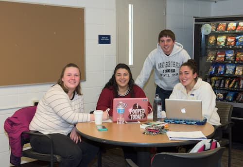 Four students working on two laptops in Chase dormitory common area