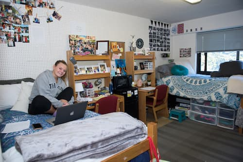 Student working on laptop in Chase dormitory room