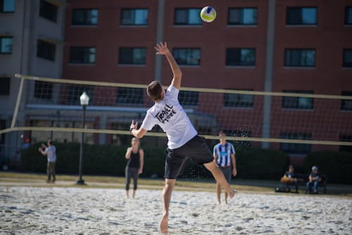 Students playing volleyball outside of Chase dormitory