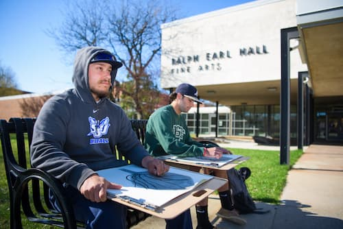 Art students sketching outside of Ralph Earl Hall