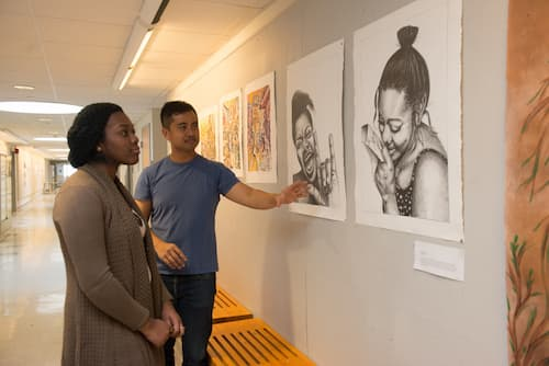 Woman being shown student artwork on display in hallway
