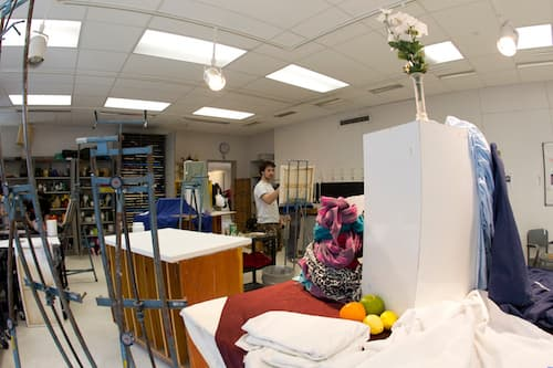 Wide shot of student painting in classroom showing still lifes
