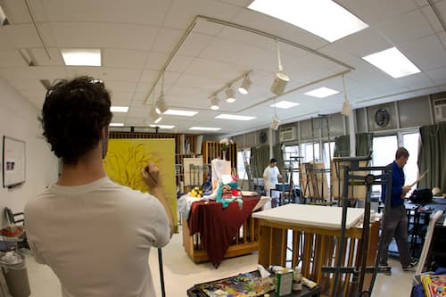 Student painting in classroom with other students in background