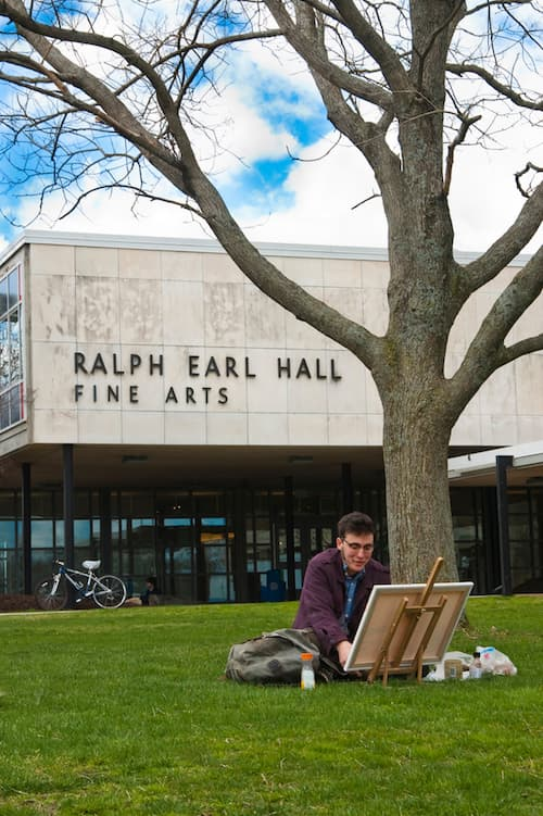Student working on artwork on lawn in front of Ralph Earl Hall