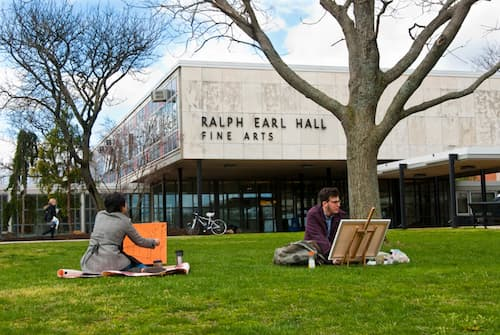Two students working on artwork on lawn in front of Ralph Earl Hall