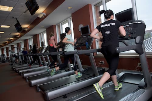 Students running on treadmills in Fitness Center