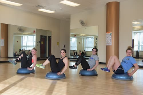 Students performing leg exercises in Fitness Center