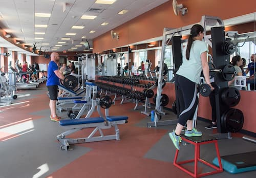 Wide shot of students lifting weights in Fitness Center