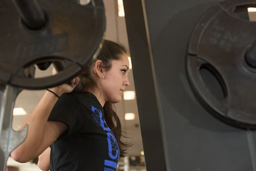 Side shot of female student lifting weights in Fitness Center