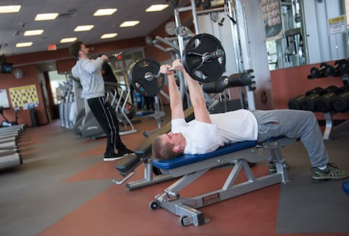 Two students lifting weights in Fitness Center