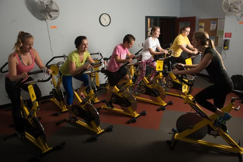 Instructor leading stationary bicyclists in Fitness Center