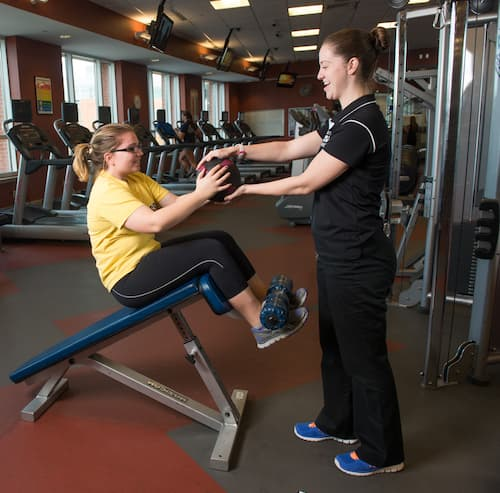 Staff member helping student with exercise routine
