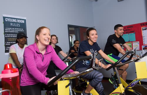 Six students riding stationary bicycles in Fitness Center