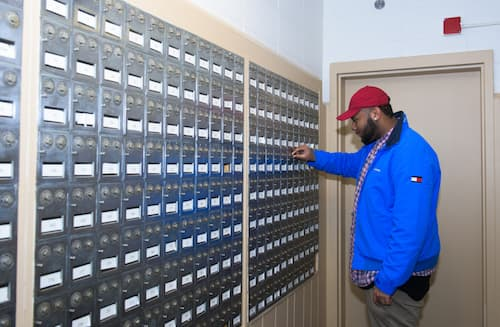 Male student checking mail in Hickerson dormitory mail room