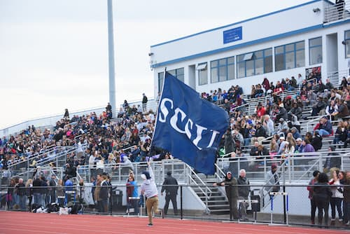 A student waving a SCSU flag