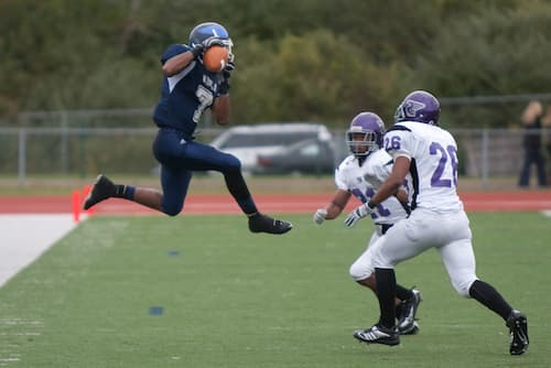 SCSU football athlete jumping
