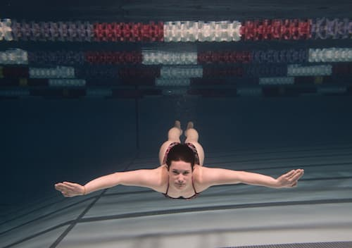 A student posing underwater