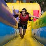 A student running through an inflatable obstacle course