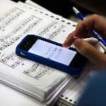 A student with music sheets and a phone