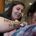 Student getting message written on arm with marker