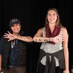 Two students showing off message written on one arm