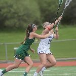 Two female lacrosse players, one in white and one in green uniforms extending sticks in air