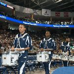 Marching band drummers playing in a large auditorium