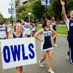 cheerleaders walking in a parade, one holding an OWLs sign