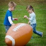 two children playing with a large football balloon