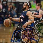 Two basketball players on wheelchairs during a game, one dribbling a ball