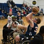 Basketball players on wheelchairs, one throwing a ball