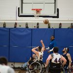 Basketball players on wheelchairs, ball in mid-air