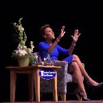 Robin Roberts sitting on a chair with hands up