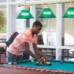 A student organizing the pool balls into the triangle