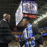 Derreck Kayongo shakes hands with a graduating student