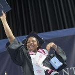 Woman holding up her diploma sleeve during commencement smiling