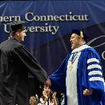 Joe Bertolino shakes hands with a graduating student