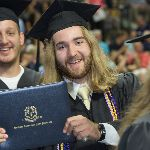Man holding his diploma sleeve smiling