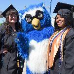Two graduates next to Otus the owl